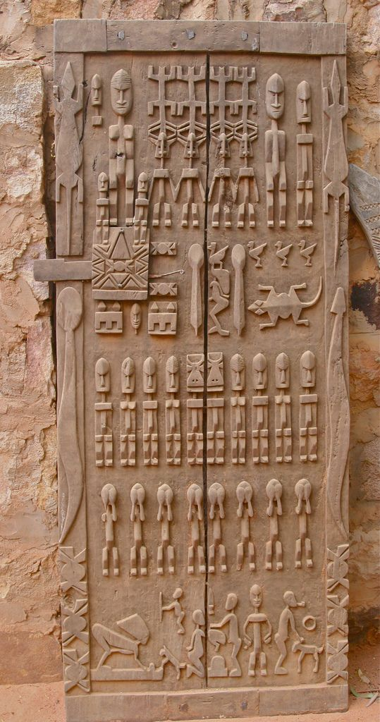 Since the Dogon language is oral, the Dogon often record their history in wood carvings, such as this door. This door deals with Dogon Cosmology and the Dogon migration that took place during the 12th to 15th centuries from ancestral lands to their current location on the Bandiagara Escarpment.