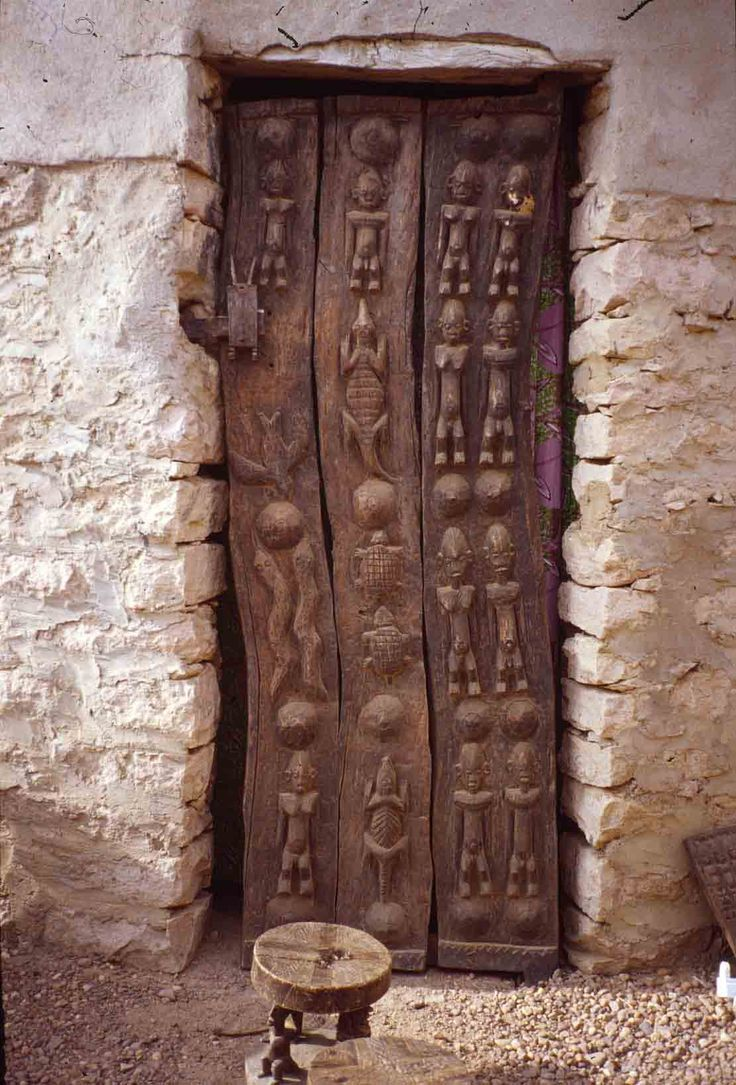 Curved Dogon door, Mali, Africa...notice the carved legs on the stool...