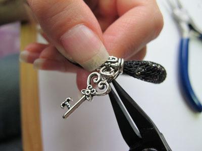 Наденьте на конец колечка подвеску и держатель и протяните колечко полностью через них: