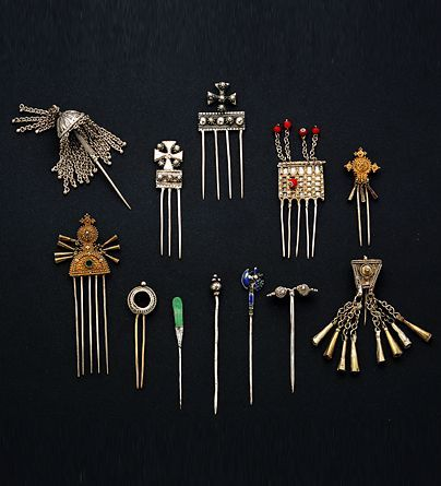 Africa   A collection of hairpins from Ethiopia   Silver, gold-plated, beads   20th century  Ethiopian women often wear hair pendants with conical bells to set off their intricately plaited hair. Rancid butter, used chiefly as a cosmetic by the Ethiopians, gives the hair its sheen. Haircombs are worn on special occasions. Finely granulated and often gold-plated, these show the influence of Yemeni Jewish goldsmiths.