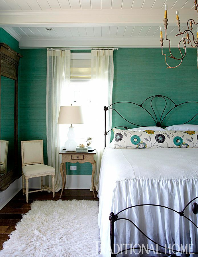 Wallpaper from Osborne & Little shrouds the room in a lovely turquoise hue—a color repeated on the floral accent pillow.