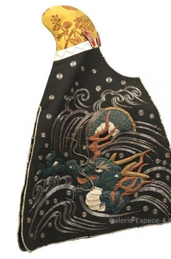Daimyo's wife headdress used during fires. The yellow wool hat is ornated with a flowered branches pattern, of European inspiration, perhaps from the Netherlands. The shi- koro is embroidered in relief with a dragon coming from foaming waves. The fukigaeshi are embroidered with a mon of sagari fuji ni kiri type (kiri flower within a wisteria flower pointing down). End of Edo.